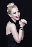 Herrliche junge blonde Frau mit einer kreativen Frisur Sie lacht Stockfotografie