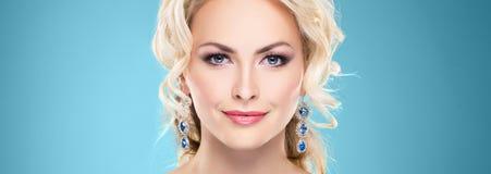 Herrliche, junge blonde tragende Saphirkrone und -ohrringe über g Stockfoto