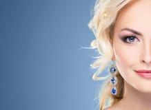 Herrliche, junge blonde tragende Saphirkrone und -ohrringe über g Lizenzfreies Stockfoto