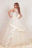 Herrliche junge Braut mit dem blonden gelockten Haar, trägt elegantes Hochzeitskleid und Krone Lizenzfreie Stockfotos
