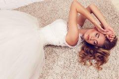 Herrliche junge Braut mit dem blonden gelockten Haar, trägt elegantes Hochzeitskleid und Krone Stockbilder