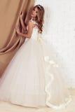 Herrliche junge Braut mit dem blonden gelockten Haar, trägt elegantes Hochzeitskleid und Krone Lizenzfreie Stockfotografie