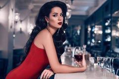 Herrliche junge Brunettefrau im roten Kleid mit Wein Stockfotos