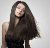 Herrliche junge Frau mit dem langen, glänzenden Haar Stockbild