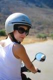 Herrliche junge Frau auf dem tragenden Sturzhelm des Rollers Stockfotografie