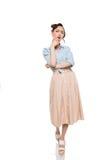Herrliche junge Frau in der Bluse und Rock stehen mit der Hand auf Kinn Stockbild