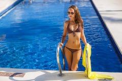 Herrliche junge Frau, die im Bikini mit gelbem pareo nahe Swimmingpool aufwirft lizenzfreie stockfotos