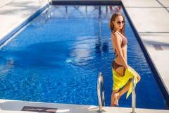 Herrliche junge Frau, die im Bikini mit gelbem pareo nahe Swimmingpool aufwirft Stockfoto