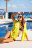 Herrliche junge Frau, die im Bikini mit gelbem pareo nahe Swimmingpool aufwirft Stockbilder