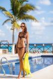 Herrliche junge Frau, die im Bikini mit gelbem pareo nahe Swimmingpool aufwirft lizenzfreie stockbilder