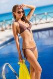 Herrliche junge Frau, die im Bikini mit gelbem pareo nahe Swimmingpool aufwirft stockfotografie