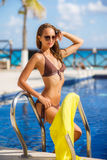 Herrliche junge Frau, die im Bikini mit gelbem pareo nahe Swimmingpool aufwirft stockfotos