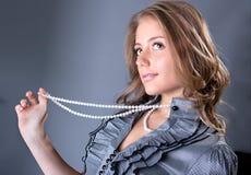 Herrliche junge Frau, die mit weißer Perle aufwirft Stockfoto