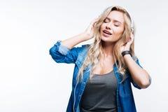 Herrliche junge Frau, die Musik in den Kopfhörern hört Stockfoto