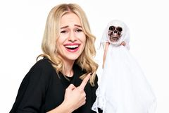Herrliche junge Frau im Hexenkostüm, das skeleton Dekoration Halloweens einen Finger auf ihn lachend und zeigend hält Ein grimmig lizenzfreie stockfotografie