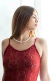 Herrliche junge Frau im roten Kleid nahe des Fensters Stockfotografie