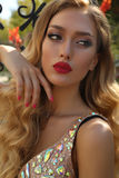 Herrliche junge Frau mit dem blonden gelockten Haar im luxuriösen Kleid Stockfotos