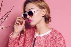 Herrliche junge Frau mit dem blonden gelockten Haar und zartem Make-up, in der eleganten Kleidung mit Zubehör Lizenzfreie Stockbilder