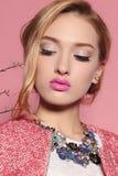 Herrliche junge Frau mit dem blonden gelockten Haar und zartem Make-up, in der eleganten Kleidung mit Zubehör Stockbild