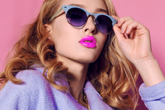 Herrliche junge Frau mit dem blonden gelockten Haar und zartem Make-up, in der eleganten Kleidung mit Zubehör Lizenzfreies Stockbild