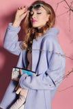Herrliche junge Frau mit dem blonden gelockten Haar und zartem Make-up, in der eleganten Kleidung mit Zubehör Stockfotografie