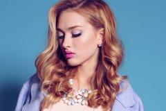 Herrliche junge Frau mit dem blonden gelockten Haar und zartem Make-up, in der eleganten Kleidung mit Zubehör Lizenzfreie Stockfotos