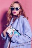 Herrliche junge Frau mit dem blonden gelockten Haar und zartem Make-up, in der eleganten Kleidung mit Zubehör Stockbilder