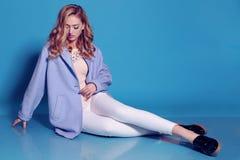 Herrliche junge Frau mit dem blonden gelockten Haar und zartem Make-up, in der eleganten Kleidung mit Zubehör Stockfoto