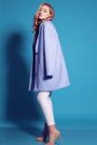 Herrliche junge Frau mit dem blonden gelockten Haar und zartem Make-up, in der eleganten Kleidung mit Zubehör Lizenzfreies Stockfoto