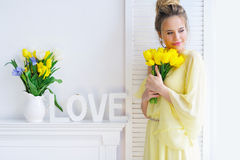 Herrliche junge Frau mit gelben Tulpen Lizenzfreies Stockfoto