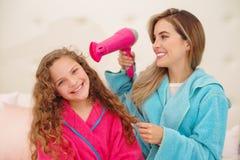 Herrliche junge Frau mit ihrer Tochter, während sie einen Haartrockner hält Entzückendes junges Mädchen, das mit ihrer Mutter an  lizenzfreies stockfoto