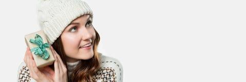 Herrliche lächelnde Frau, die kleines Geschenk hält Neugier-Weihnachtskonzeptfahne, lokalisiert Lizenzfreie Stockfotos