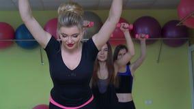 Herrliche Mädchen, die etwas Gewichte anheben und Muskeln in einer Turnhalle 4k Arbeits stock video