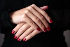 Herrliche Maniküre, clssic rote Farbnagellack, Nahaufnahmefoto Frau überreicht dunklen Hintergrund stockfotos