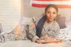 Herrliche Militärfrau, die mit einer Tablette aufwirft Stockfotos