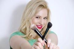 Herrliche natürliche blonde haltene Make-upbürsten gekreuzt Stockfotografie