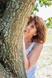 Herrliche reife Frau, die hinter einem Baum für Metapher der Diskretion sich versteckt Lizenzfreie Stockfotografie