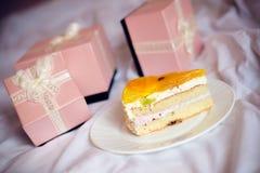 3 herrliche schöne Luxusrosageschenke und köstliche Scheibe des Kuchens auf einer Platte auf dem weißen Betthintergrund Stockfoto