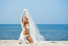 Herrliche, sexy blonde Aufstellung mit dem Schlag silk auf dem Strand Lizenzfreies Stockbild