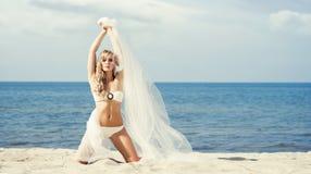 Herrliche, sexy blonde Aufstellung mit dem Schlag silk auf dem Strand Lizenzfreies Stockfoto