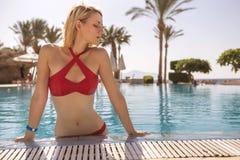 Herrliche sexy blonde dünne Frau mit Sitzkörper in rotem Badeanzugschalter Lizenzfreies Stockbild