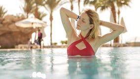 Herrliche sexy blonde dünne Frau mit Sitzkörper in rotem Badeanzugschalter Lizenzfreie Stockfotografie