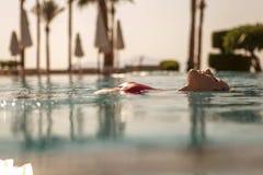Herrliche sexy blonde dünne Frau mit Sitzkörper in rotem Badeanzugschalter Lizenzfreies Stockfoto