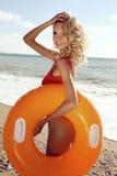 Herrliche sexy Frau mit dem blonden gelockten Haar im roten Badeanzug Stockfotos
