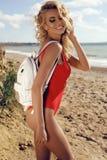 Herrliche sexy Frau mit dem blonden gelockten Haar im roten Badeanzug Stockbilder
