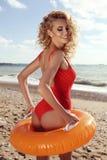 Herrliche sexy Frau mit dem blonden gelockten Haar im roten Badeanzug Lizenzfreie Stockfotografie
