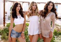 Herrliche sexy Frauen in der zufälligen Kleidung, die auf Strand aufwirft Stockfotos
