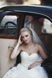 Herrliche stilvolle blonde Braut, die im Retro- schwarzen Auto im Weiß aufwirft Lizenzfreie Stockfotos