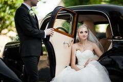 Herrliche stilvolle blonde Braut, die im Retro- schwarzen Auto mit gro aufwirft Lizenzfreies Stockfoto