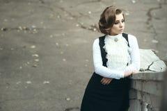 Herrliche traurige Frau mit der eleganten viktorianischen Frisur, die auf der alten Treppe beiseite mit der Eisenbahn befördert u Stockfotos